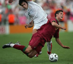 Frankfurt am Main, GERMANY: Portuguese forward Cristiano Ronaldo (R) goes airborne challenged by Iranian midfielder Mehrzad Madanchi (L) during the World Cup 2006 group D football game Portugual vs.Iran 17 June 2006 at Frankfurt stadium. AFP PHOTO BEHROUZ MEHRI (Photo credit should read BEHROUZ MEHRI/AFP/Getty Images)