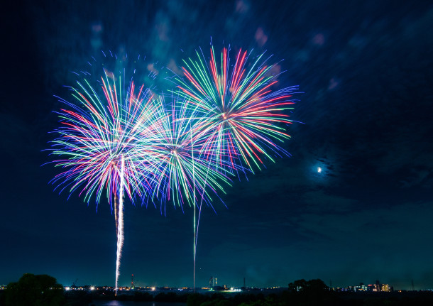 Fireworks explode in the sky on a moonlit night in Japan